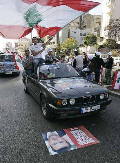 Un coche de seguidores del partido del ministro libanés de Industria, Pierre Gemayel, pasa por encima de un poster del presidente sirio Bashar al-Achad.