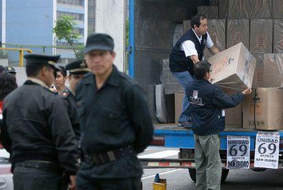 Varias personas trasladan las papeletas a un centrol electoral de la ciudad de Lima.
