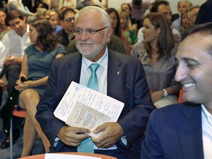 Juan Cotino en el pasado Comité Regional del PP, la pasada semana, con un libro de Luis Lucia en las manos.