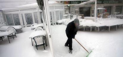 Un trabajador retira la nieve de la puerta de un bar en Navacerrada.