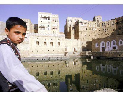Un niño observa una antigua cisterna de agua en la ciudad yemení de Hababa.