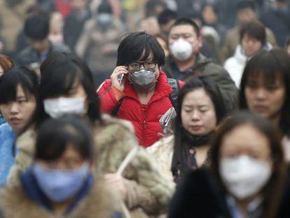 Transeúntes caminan con mascarilla por las calles de Pekín.