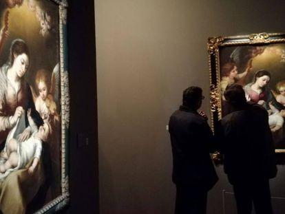 Dos visitantes miran 'La Virgen de la faja', de Miguel de Tovar. A la izquierda, la de Murillo.