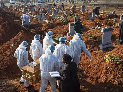 El ataúd de una víctima del virus Covid-19 Corona que fue llevado a su tumba por familiares en un cementerio de Johannesburgo (Sudáfrica) el 24 de julio de 2020