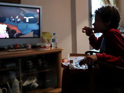 Un niño come un trozo de pizza  mientras ve la televisión en Madrid.