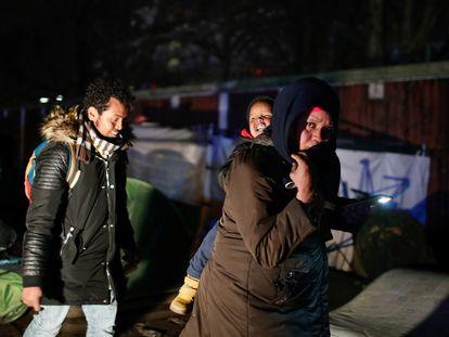 Una mujer con un niño y otras personas migrantes son desalojados por la policía de un asentamiento informal en La Porte d'Aubervilliers en Paris, Francia, en enero de 2020.