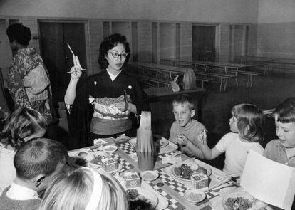 La profesora Michiko Fujii, vestida con kimono y obi, muestra a sus alumnos cómo comer los platos orientales en la cafetería del colegio en Denver (Estados Unidos), en 1969. |