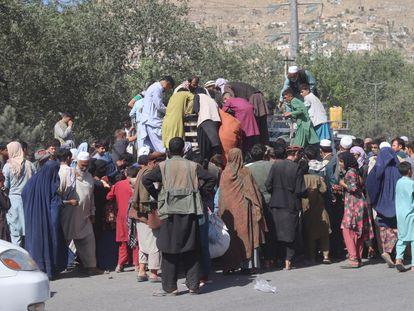 Desplazados internos por los combates rodean un camión en Kabul para recibir comida el 10 de agosto.