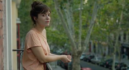 Fotograma de la película La virgen de agosto de Jonás Trueba donde la protagonista se asoma a la calle Rivera de Curtidores.
