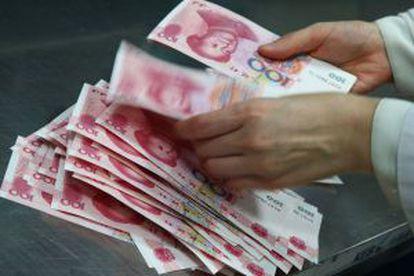Un empleado de un banco chino cuenta billetes de 100 yuanes