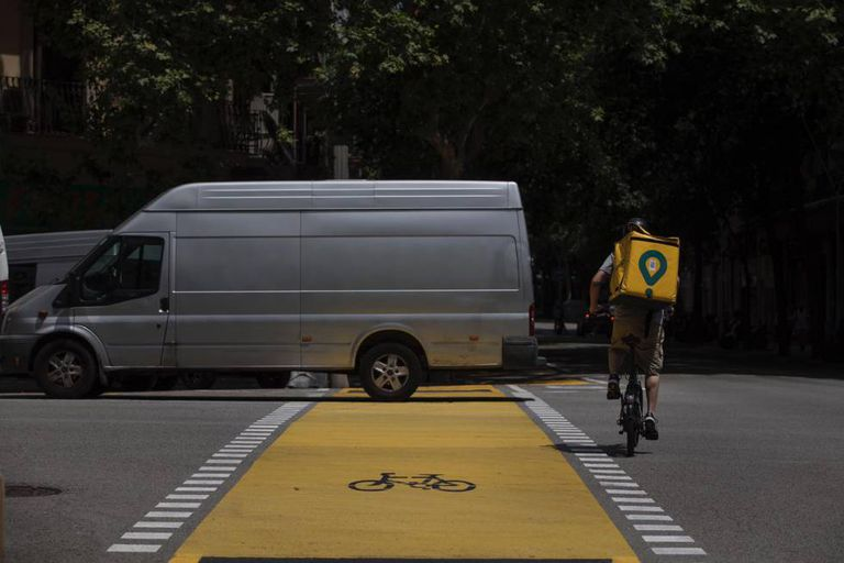 Un repartidor de Glovo y una furgoneta en el nuevo carril bici de Pau Claris.