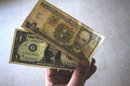 Un billete de un peso cubano con la imagen de José Martí sobre otro de un dólar con la imagen de George Washington.