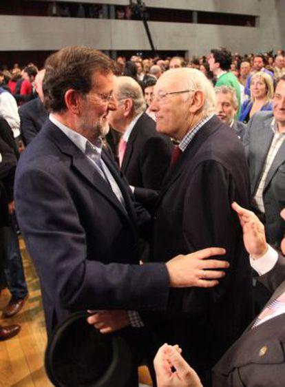Rajoy saluda a José Manuel Beccaria (derecha), en un mitin en Santiago en abril de 2010.