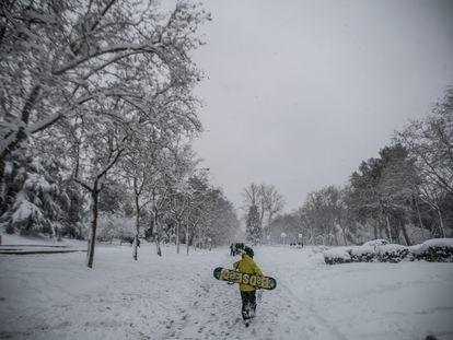 Un joven con una tabla de 'snow', en el parque del Paraíso de Madrid durante el temporal 'Filomena'.