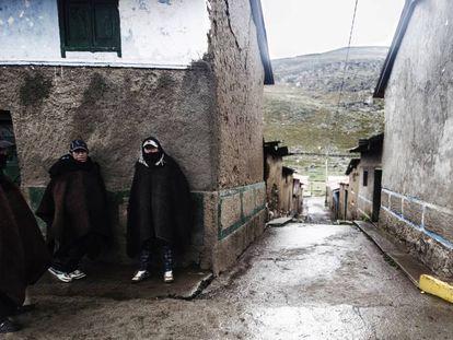 Tres hombres se protegen del frío en los Andes peruanos.