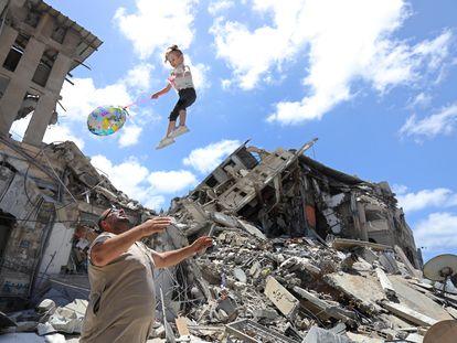 Un palestino juega con una niña junto a los escombros de una vivienda bombardeada, el sábado en Gaza.