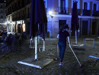 Una trabajadora recoge la terraza de una cafetería de Madrid pasada la medianoche.