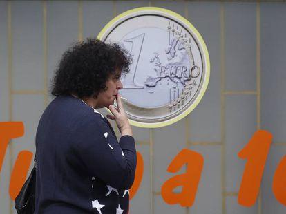 Una mujer fuma junto a un comercio de Lisboa.
