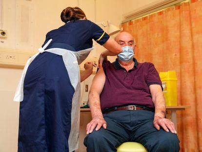 Brian Pinker es vacunado con la inmunización de Oxford y AstraZeneca en el Hospital Universitario de Oxford este lunes.