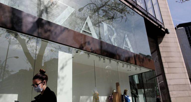 Una mujer con mascarilla pasa junto a una tienda de Zara en Madrid.