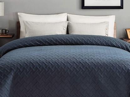 Con un diseño geométrico en relieve, esta colcha de verano se presenta en azul marino, blanco, gris y negro.