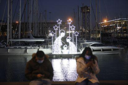 Dos personas junto a un Belén luminoso el día de la inauguración del encendido de luces de la segunda edición de 'Nadal al Port', en el puerto de Barcelona, el 2 de diciembre.