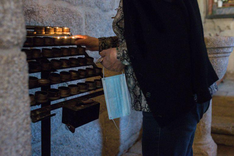 Una mujer que lleva una mascarilla en la mano enciende una vela durante la celebración de misa en la iglesia parroquial de Requiás y Guntumil (Muiños, Ourense).