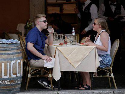 Dos turistas comen en la terraza de un restaurante del centro de Roma