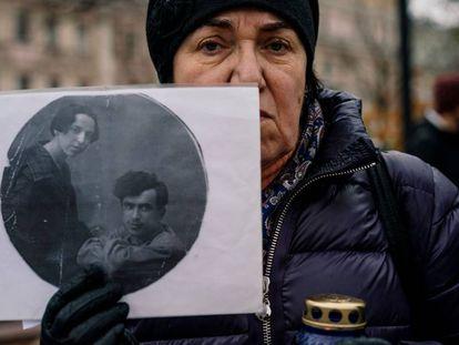 Una mujer sostiene la fotografía de sus familiares, represaliados por el estalinismo en la ceremonia en memoria de las víctimas, este martes en Moscú.