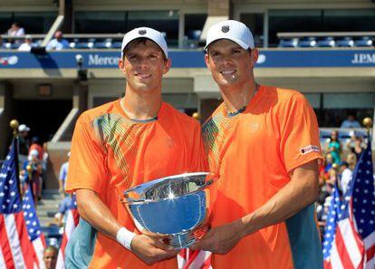 Mike Bryan y Bob Bryan posan con el trofeo de campeones del US Open.
