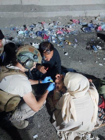 Un médico español atiende a un niño de un refugiado herido al entrar a la base.