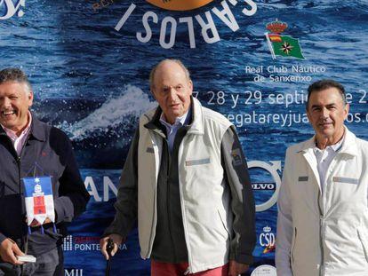 El rey emérito Juan Carlos I, en el centro, con el alcalde de Sanxenxo, Telmo Marín, a la izquierda, y el presidente del club naútico Pedro Campos.