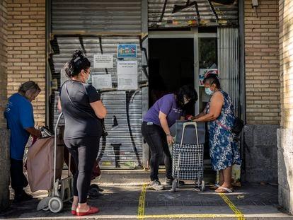 Un grupo de personas en el banco de alimentos Gran Avenida 24, en el barrio de Orcasitas (Madrid).