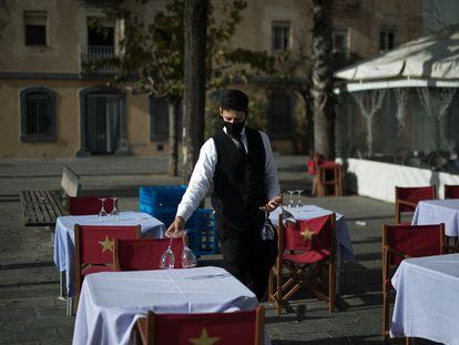 Un camarero prepara las mesas de la terraza para el turno de las comidas en Barcelona.