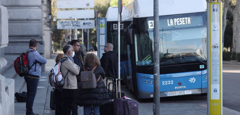 Varias personas esperan el autobús en una parada de la EMT en Cibeles, en Madrid, en una foto de archivo.