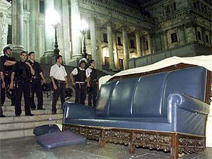 La Policía custodia el Parlamento frente al sofá sacado por los manifestantes del interior de la sede legislativa.