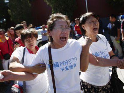 Familiares de los pasajeros del vuelo MH370 de Malaysia Airlines lloran durante una ceremonia en Pekín cuando se cumplen seis meses de la desaparición del avión.