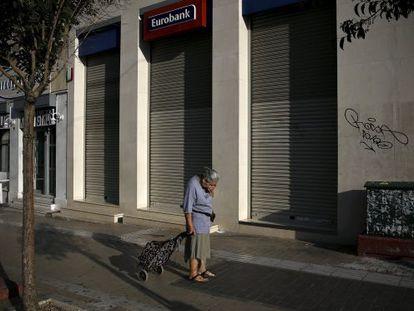 Una mujer pasa delante de una sucursal bancaria cerrada, el lunes en Atenas.