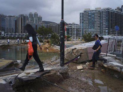 Varias personas caminan entre los destrozos causados por el tifón Mangkhut en el paseo marítimo de Hong Kong.