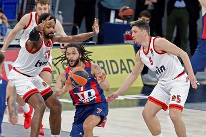 Henry pasa el balón ante la defensa de Larentzakis y Jean-Charles