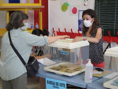 Una electora deposita su voto en un colegio electoral en Marsella, Francia, durante la segunda vuelta de las elecciones regionales.