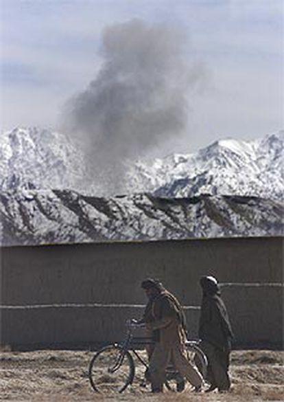 Varios civiles afganos pasean mientras las bombas caen en las montañas de Surmad.