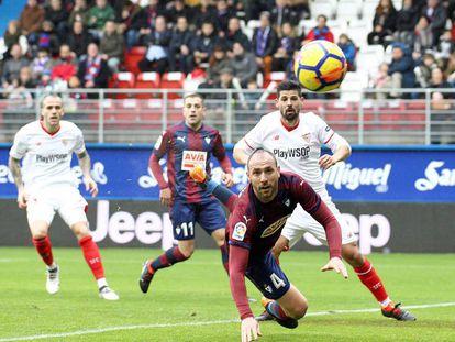 Iván Ramis, del Eibar, se lanza a por la pelota ante la mirada del sevillista Nolito.