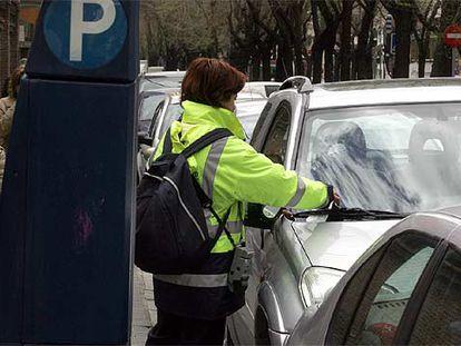 Una controladora coloca una denuncia en un turismo en la calle de Juan Bravo, en diciembre pasado.