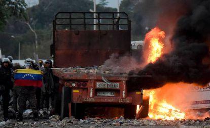 Fuerzas de seguridad venezolanas muestran una bandera junto a camión quemado con ayuda humanitaria.