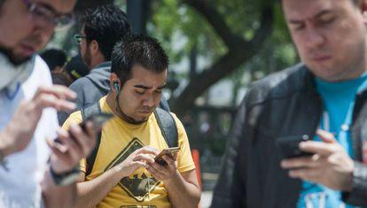 Un grupo de paseantes utiliza su celular en Ciudad de México.