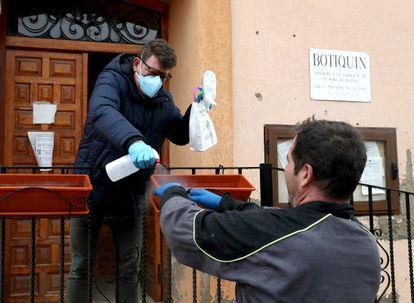 El farmaceutico de La Yunta (Guadalajara) desinfecta las manos a un vecino después de entregarle sus medicamentos a la entrada del consultorio.
