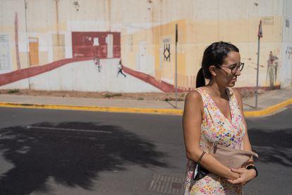 Sheyma Mohamed fotografiada frente a la pintura en la pared del presidio de Melilla, una creación obra de los propios internos que imita el aspecto de una calle.