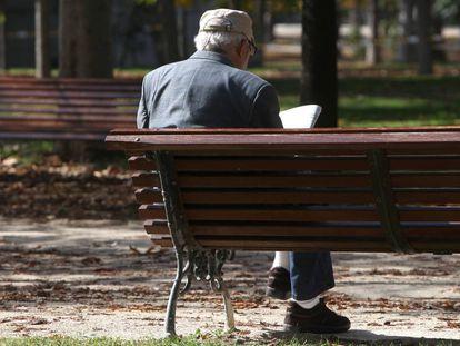 Un hombre lee el periódico en un parque de Madrid.
