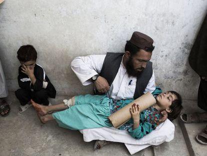 Un hombre sujeta a su hija de 8 años mientras espera en el hospital Boost de Lashkar Gah, en la provincia de Helmand.